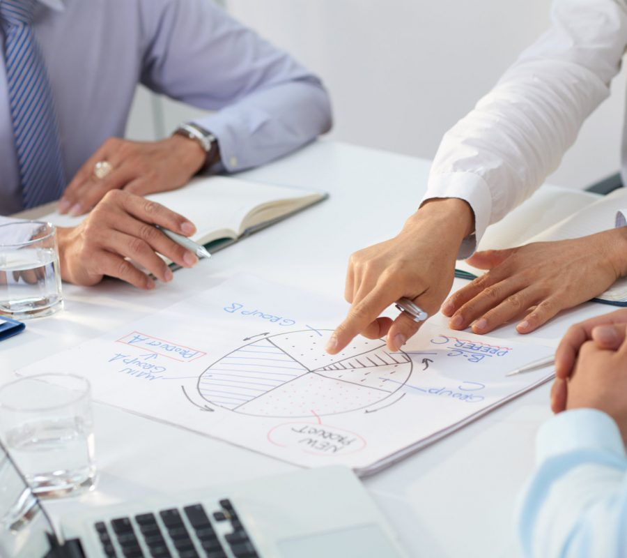 Cropped image of business team discussing diagram at meeting